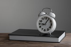 Alarm clock standing on of closed book