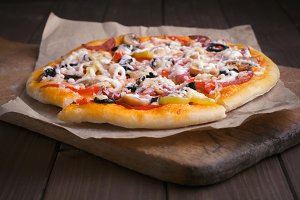 Pizza on cutting board and wooden table background