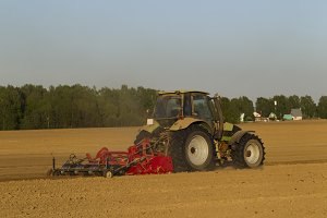 The tractor in the field on agricultural operations