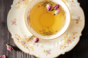 Vintage cup of tea with rosebuds, on black background