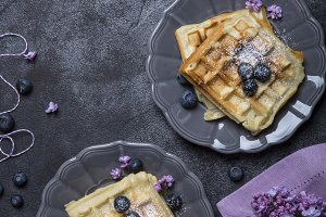 Vegan crispy waffles with blueberries on a dark background
