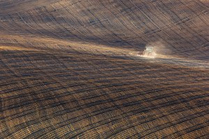 tractor plowing a striped field