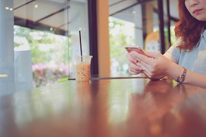 Woman using smart phone in cafe