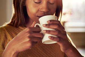 Attractive young woman savoring a cup of coffee