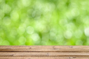 Wooden table with green bokeh