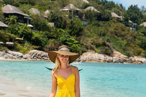 Cute lady with sun hat at the beach.
