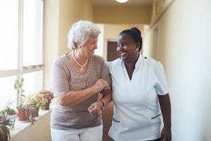 Smiling home caregiver and senior