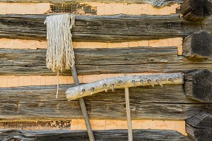 Old mop and rake against cabin