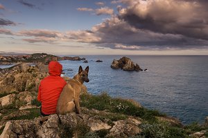 Man and dog looking at the sea