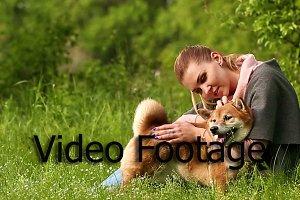 Girl hugs dog Shiba Inu