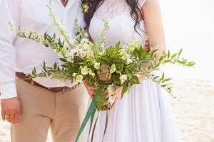 a wedding bouquet is in the hands of fiancee