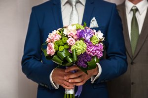 wedding bouquet in hands of the groom