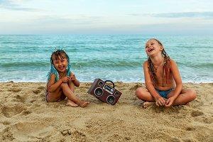 Children listen to music on the beach