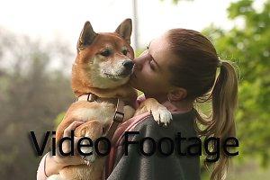 Girl holds a dog Shiba Inu
