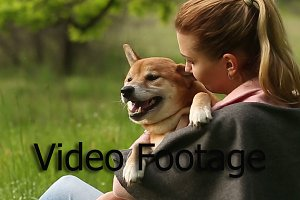 Girl biting ear dog Shiba Inu