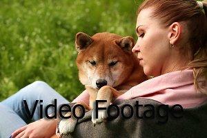 Girl gently hugs dog Shiba Inu