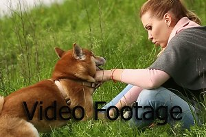 Girl holds dog leashed Shiba Inu