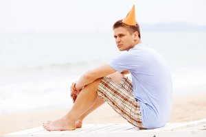 Guy in party hat on beach
