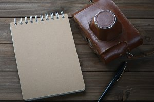 Blank notebook with fountain pen and retro camera on wooden table