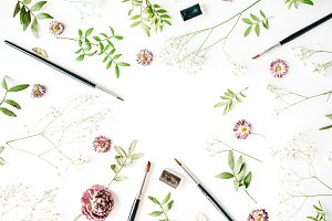 Workspace with brushes and flowers