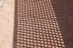 shadows with holes in the sidewalk
