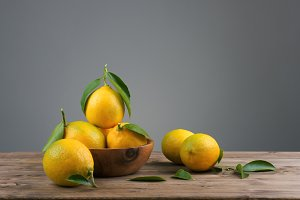 lemons with green leafs in a wooden bowl on the table