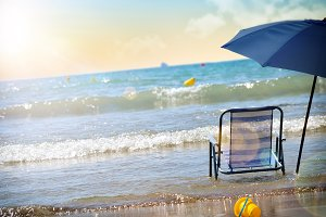 Beach chair and umbrella on water