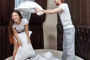 Married couple pillow fight.