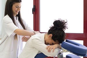 Smiling female doctor doing massage to her colleague