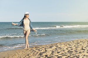 Pretty woman walking on the beach.