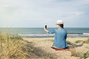 Woman take picture on the beach.
