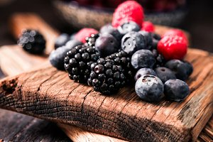 blueberries and raspberries on a wooden background