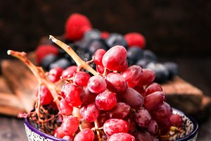 blueberries and red grapes on a wooden background