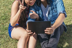 Young happy couple using tablet.