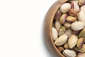 Pistachios in wooden bowl on white