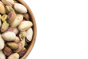 Bunch of Pistachios in wooden bowl