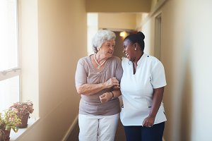 Happy female caregiver and senior