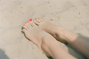 Beautiful female feet on the sand