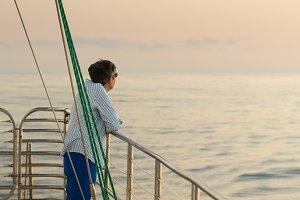 Senior woman at sunset on boat