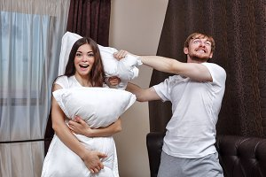 Young couple pillow fight.