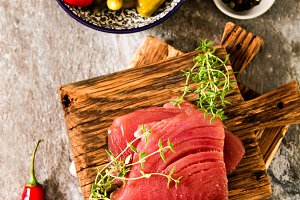Tuna steak on a wooden board with pepper and cucumber