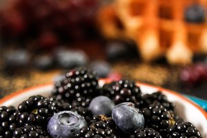 Belgian waffles with fresh berries and grapes on rustic wooden background