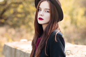 girl with red lips wearing a hat