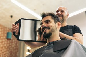 Man getting haircut by hairdresser.