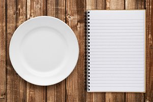 Empty plate and cookbook on table