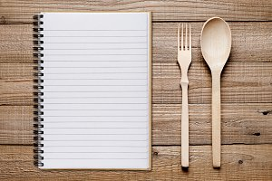 Cookbook, spoon and fork on table