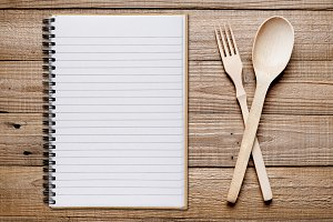 Cookbook, fork and spoon on table