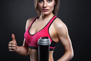 Fitness girl with shaker on a dark background