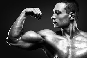 Strong and handsome young bodybuilder demonstrate his muscles an