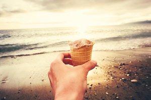 Hand with Ice-Cream on sea beach